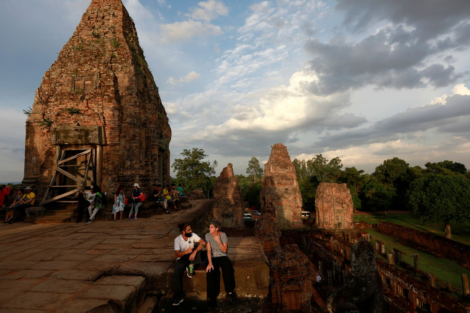 Tourists pass their time as they wait to watch the sunset, at a temple near Angkor Wat, in Siem Reap