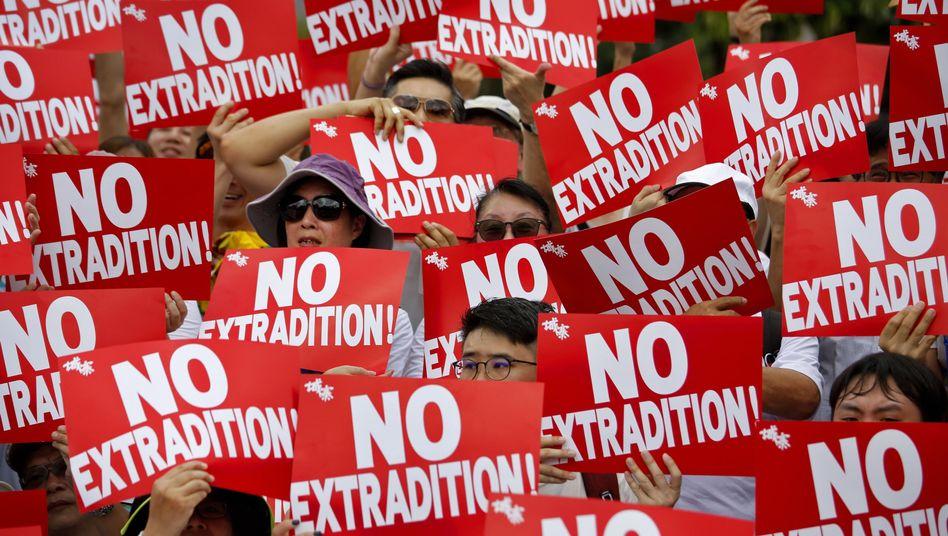 """Demonstranten halten Plakate mit der Aufschrift """"No Extradition!"""" (Keine Auslieferung)"""