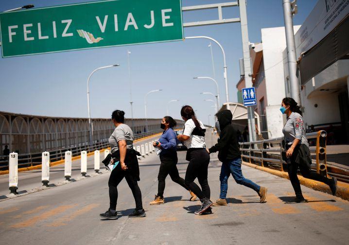 Eine Gruppe von Migrantinnen, die unter Titel 42 abgeschoben wird, passiert den Grenzübergang in Tijuana