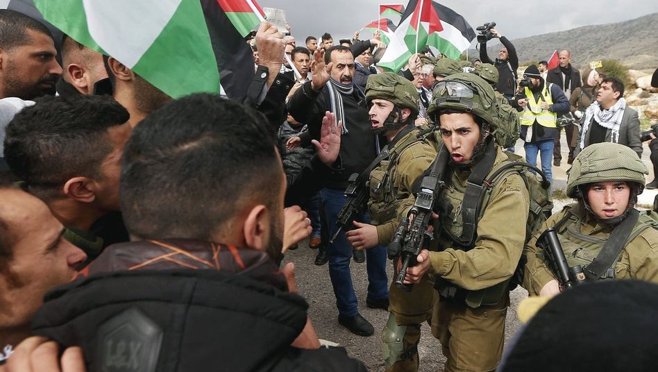 Israeli soldiers face off against Palestinian protesters in the Occupied West Bank.