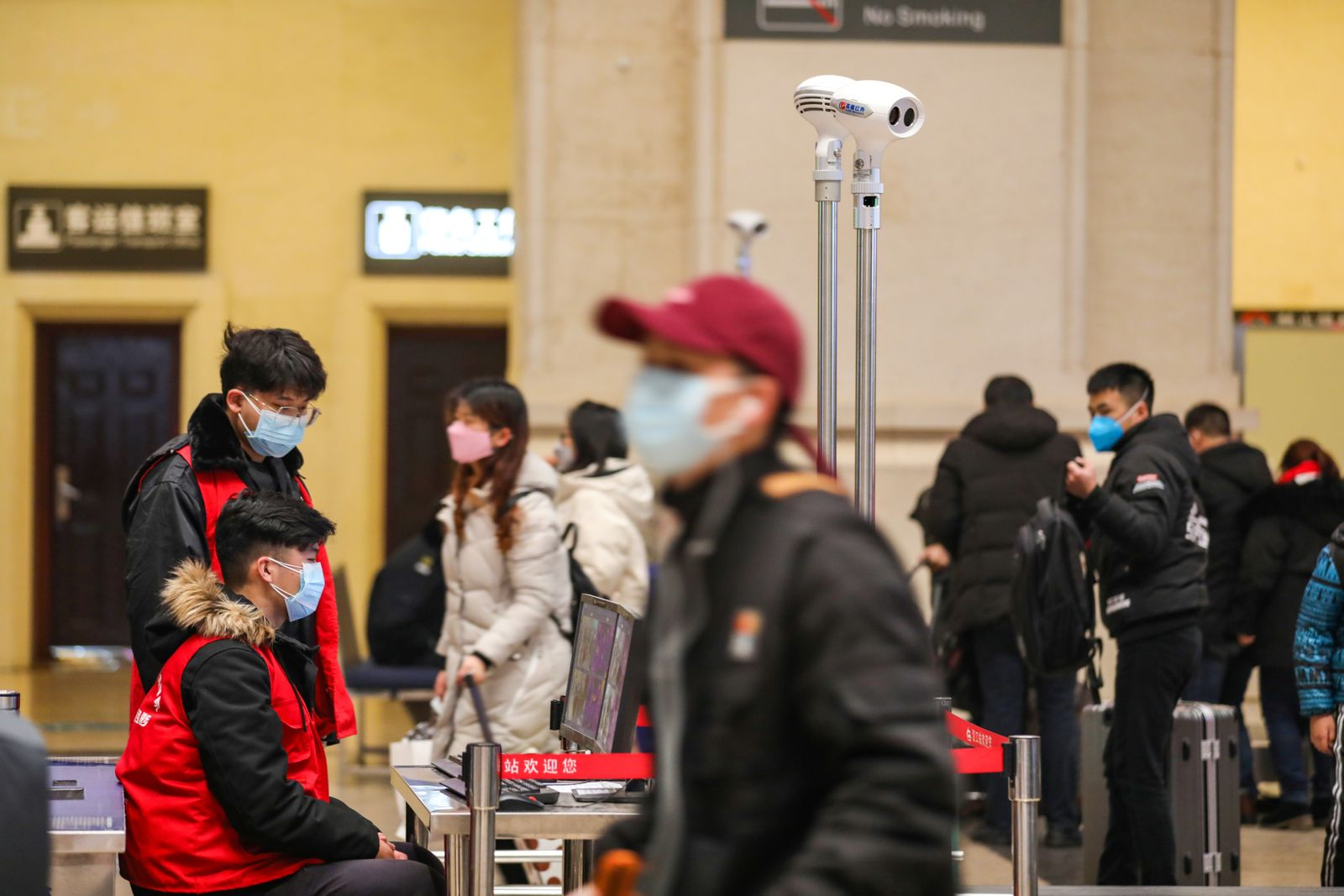 Staff members wearing masks monitor thermal scanners that detect temperatures of passengers at the security check inside the Hankou Railway Station in Wuhan
