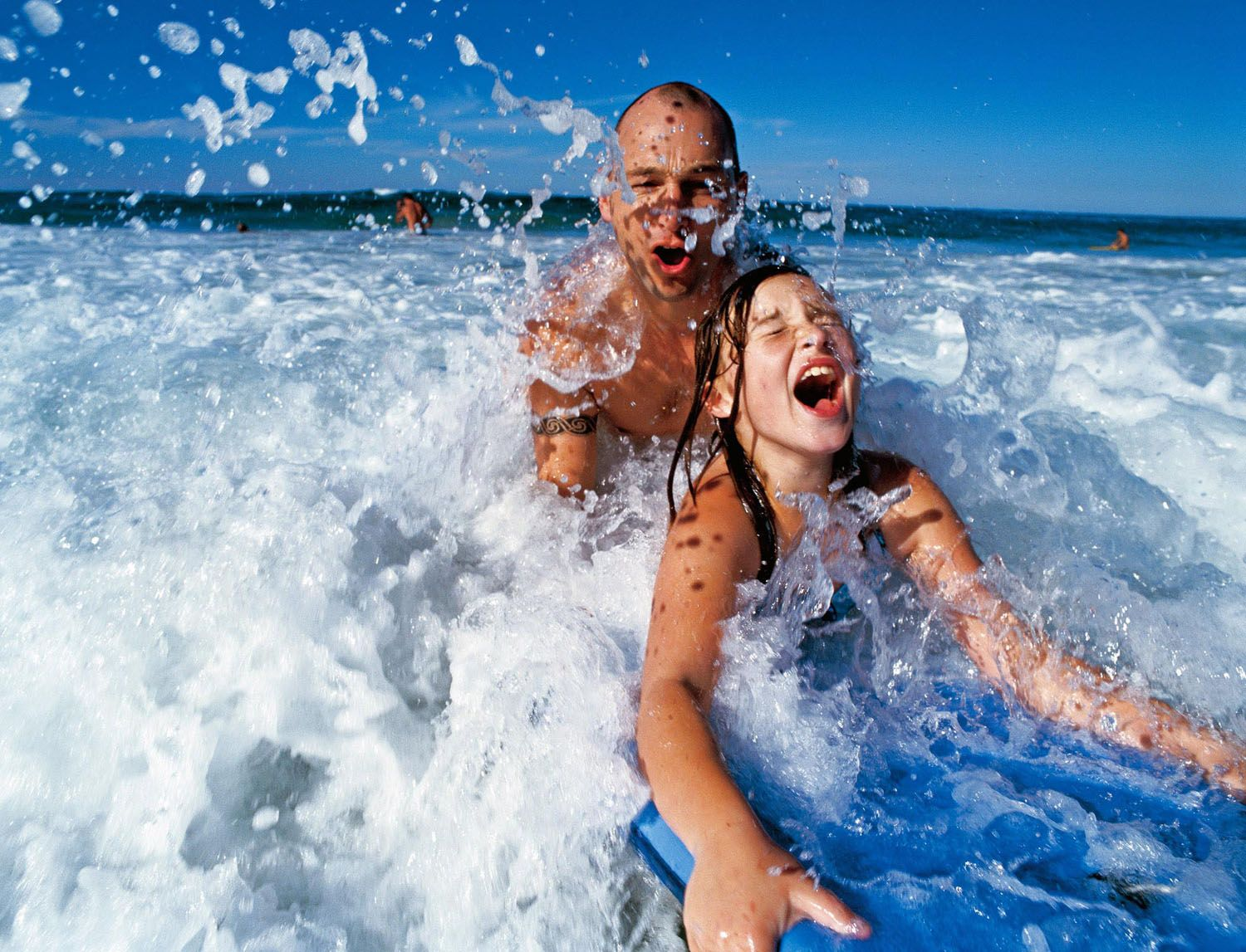 Father and daughter on a surfboard.