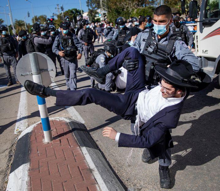 Ein israelischer Polizist trägt einen ultraorthodoxen Juden in Aschdod weg