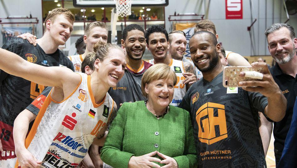 Virgil Matthews (2.v.r) von den Chemnitzer Niners macht ein Selfie mit Merkel
