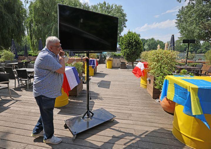 Ein Betreiber eines Biergartens in Nordrhein-Westfalen rüstet seine Terrasse für EM-Fans