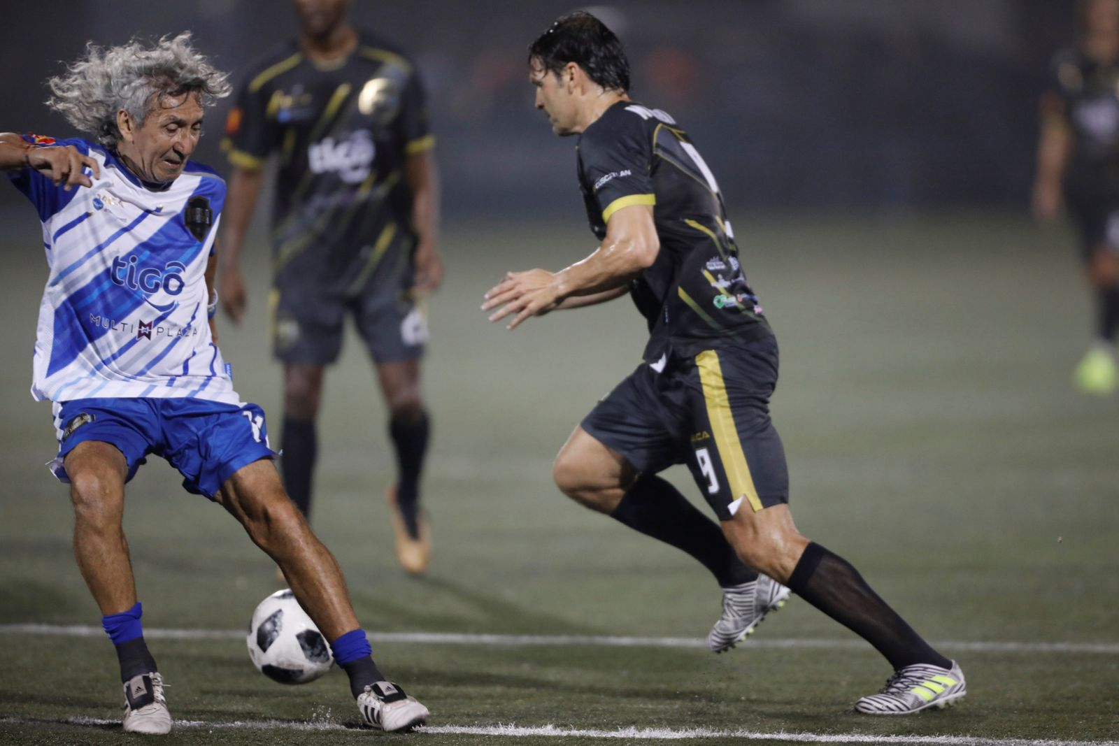 "Former Salvadorean soccer player Jorge ""Magico"" Gonzalez plays ball with former Spanish soccer player Fernando Morientes during an exhibition match at Las Delicias Stadium in Santa Tecla"