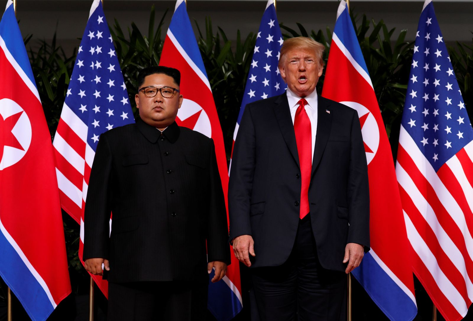 North Korea's leader Kim Jong Un stands next to U.S. President Donald Trump before their meeting in Singapore