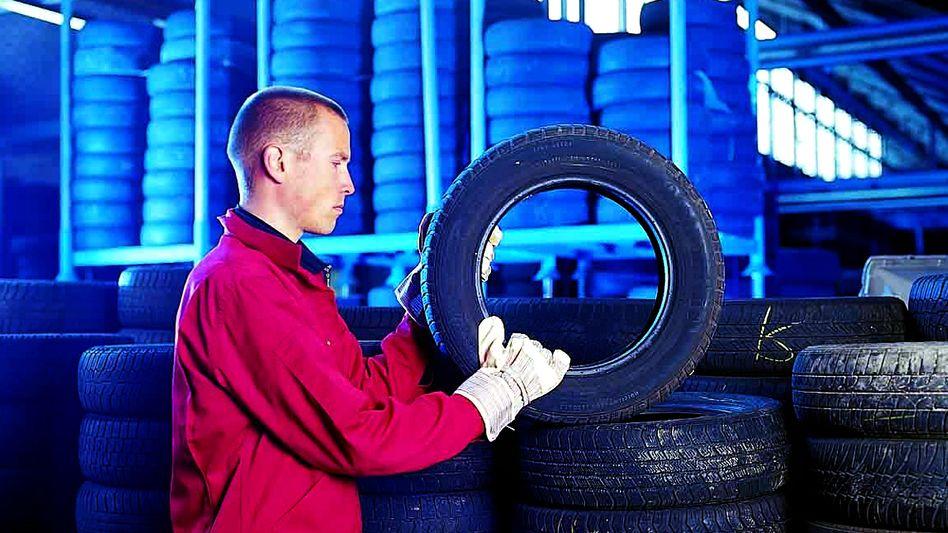 Kontrolle: Dieser Mitarbeiter eines Reifendienstes prüft einen runderneuerten Pneu