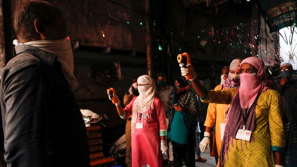 Bitte recht freundlich: Mitarbeiter des Gesundheitsamts in Mumbai messen Fieber