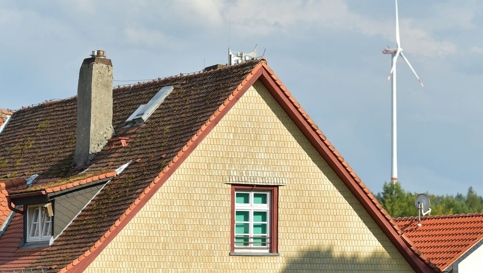 Ein Haus im hessischen Siedelsbrunn mit einem Windrad auf einer benachbarten Höhe.
