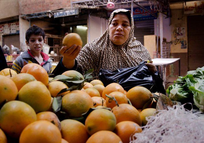 Eine Frau kauft Orangen auf einem Markt in Kairo