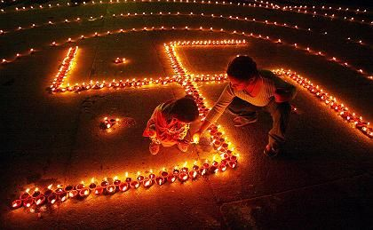 The swastika is a sacred symbol for Hindus, who are protesting its proposed ban in the EU. Here Hindus in India celebrate Diwali by lighting lamps in the shape of a swastika.