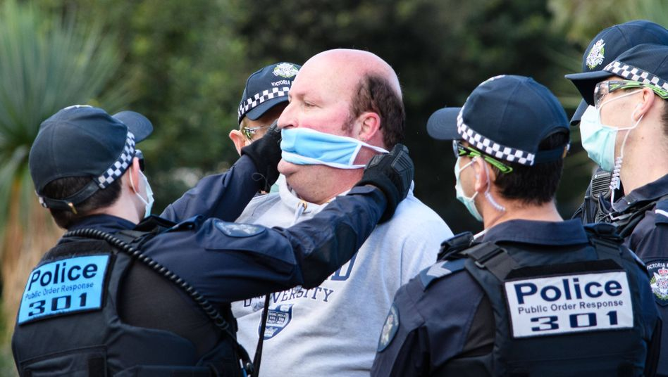 Szene aus Melbourne: Ein Mann bekommt von Polizisten einen Mundschutz verpasst