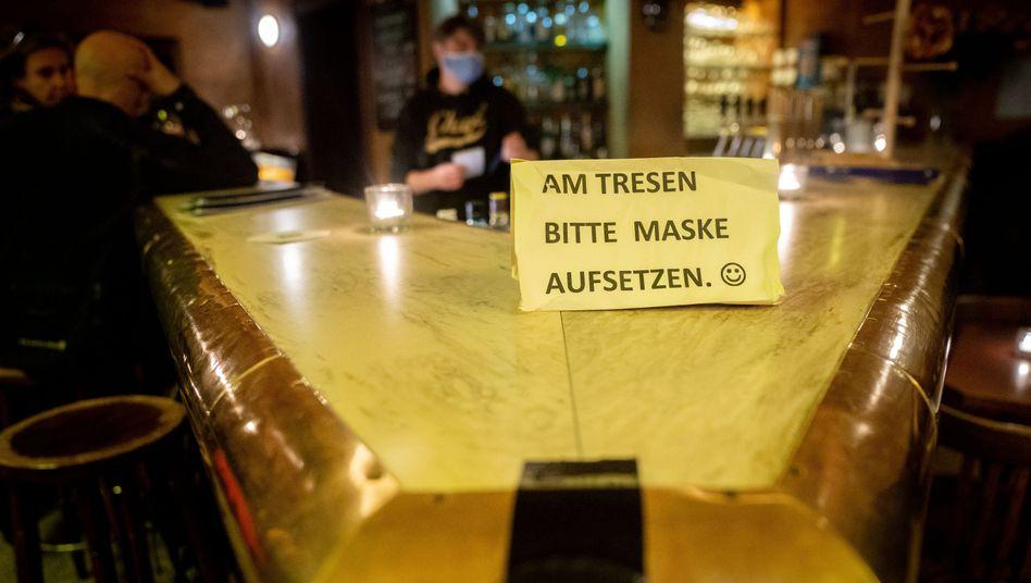 """""""Bitte Maske aufsetzen"""": Hinweisschild in einer Bar"""