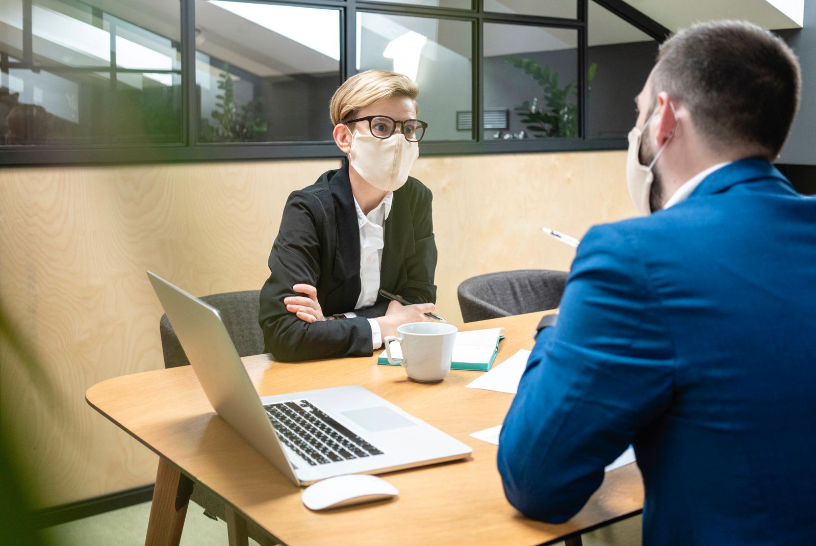 Female and male colleagues wearing masks while planning strategy at desk in board room during epidemic model released Sy