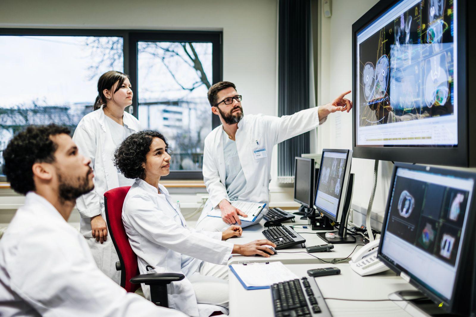 EINMALIGE VERWENDUNG Team Of Doctors Looking At Lab Results