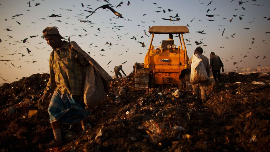 People scavenging at a dump in India: Where are the limits to growth?