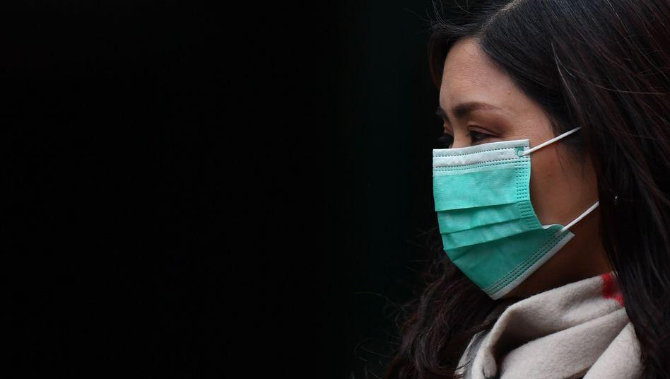 Eine Frau schützt sich in Londons China Town mit einer Atemmaske