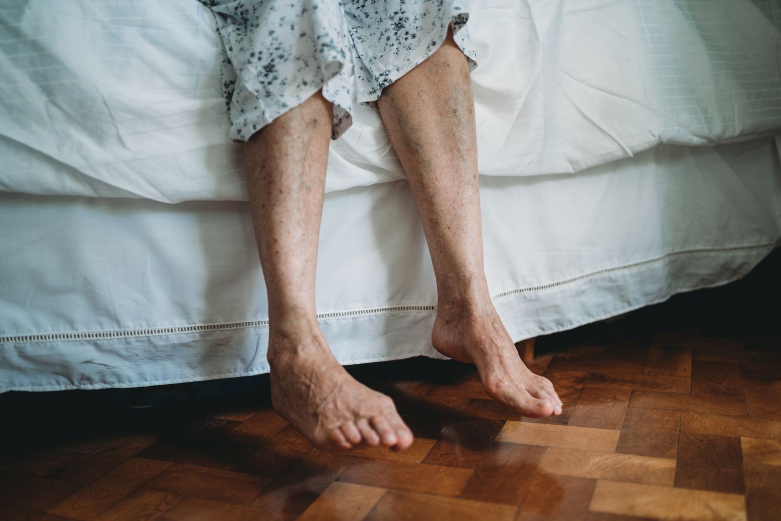 Front view of a senior lady's feet on the side of bed