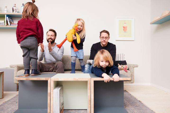 """Bekind-Gründer Philip Dabrowski und Lars Theenhaus mit ihrem Möbelstück """"EINS"""" - und ihren Kindern"""