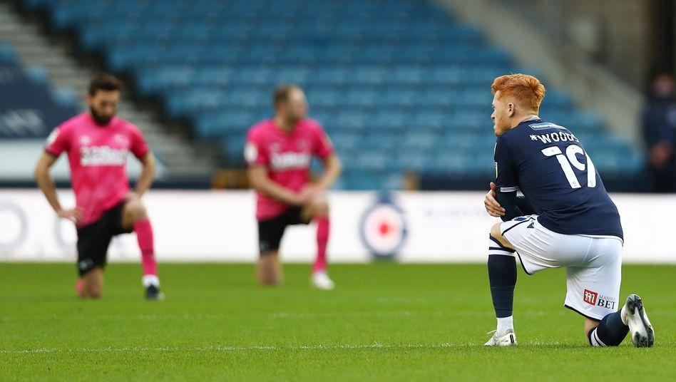Spieler der Zweitligisten Millwall und Derby knien zu Spielbeginn