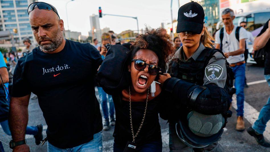 Sicherheitskräfte in Israel führen eine Frau ab: Auslöser der Proteste war der Tod des 18-jährigen Solomon Tekah