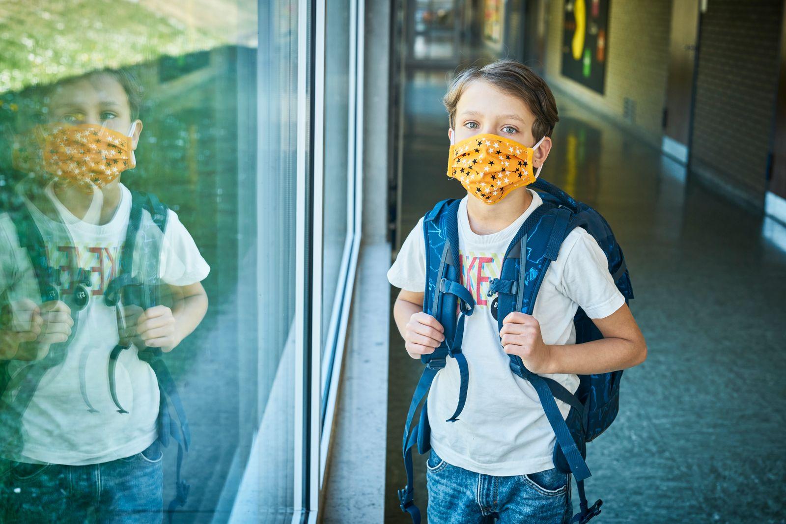 Boy wearing mask in school mirrored in window