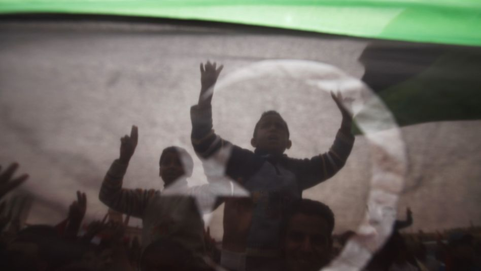 Protesters are seen through a Kingdom of Libya flag during celebrations in Tobruk following the UN resolution.