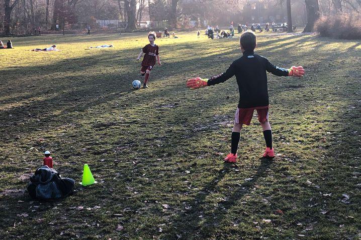 Zwei Kinder spielen Fußball auf einer Wiese