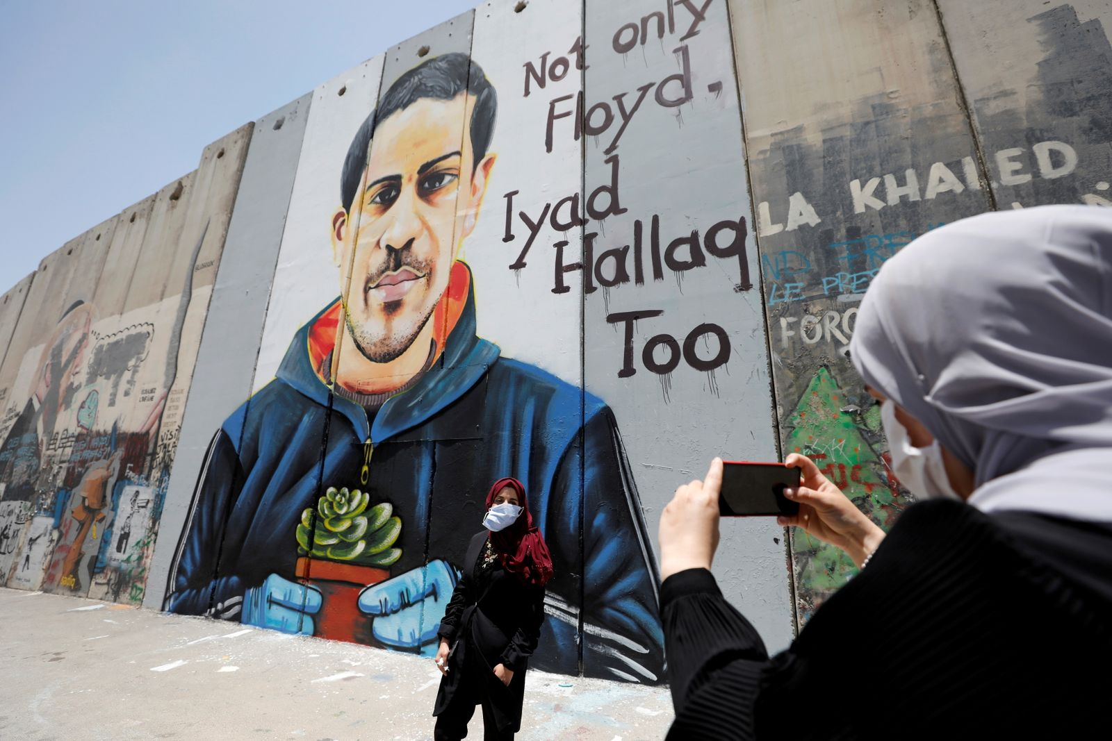 FILE PHOTO: A Palestinian woman takes pictures of her friend posing in front of the Israeli barrier with a mural depicting Iyad al-Halaq, in Bethlehem in the Israeli-occupied West Bank