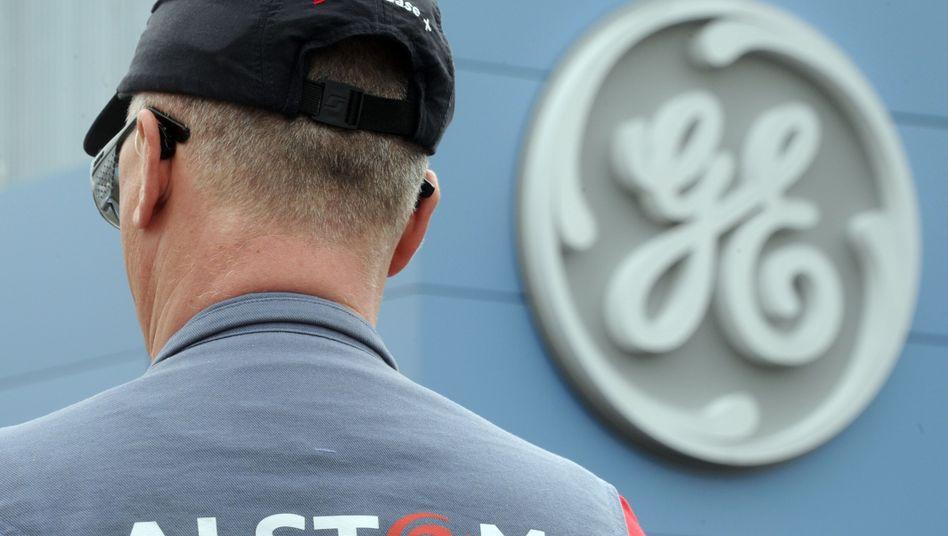 Alstom-Mitarbeiter vor GE-Logo: Der Konzern bevorzugt das Gebot des US-Multis