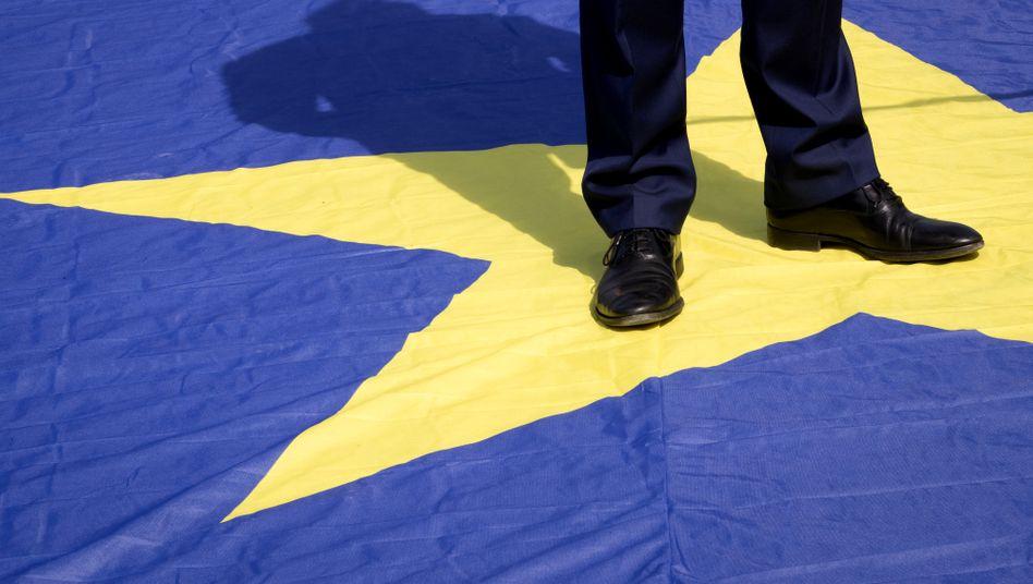 Ein Mann steht in Brüssel auf einer Europaflagge