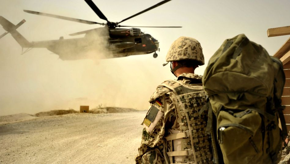 A German soldier watches a helicopter land in Afghanistan in Oct. 2011.