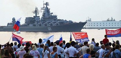 Pro-Russian supporters welcome a Russian missile cruiser Moskva to Sevastopol.