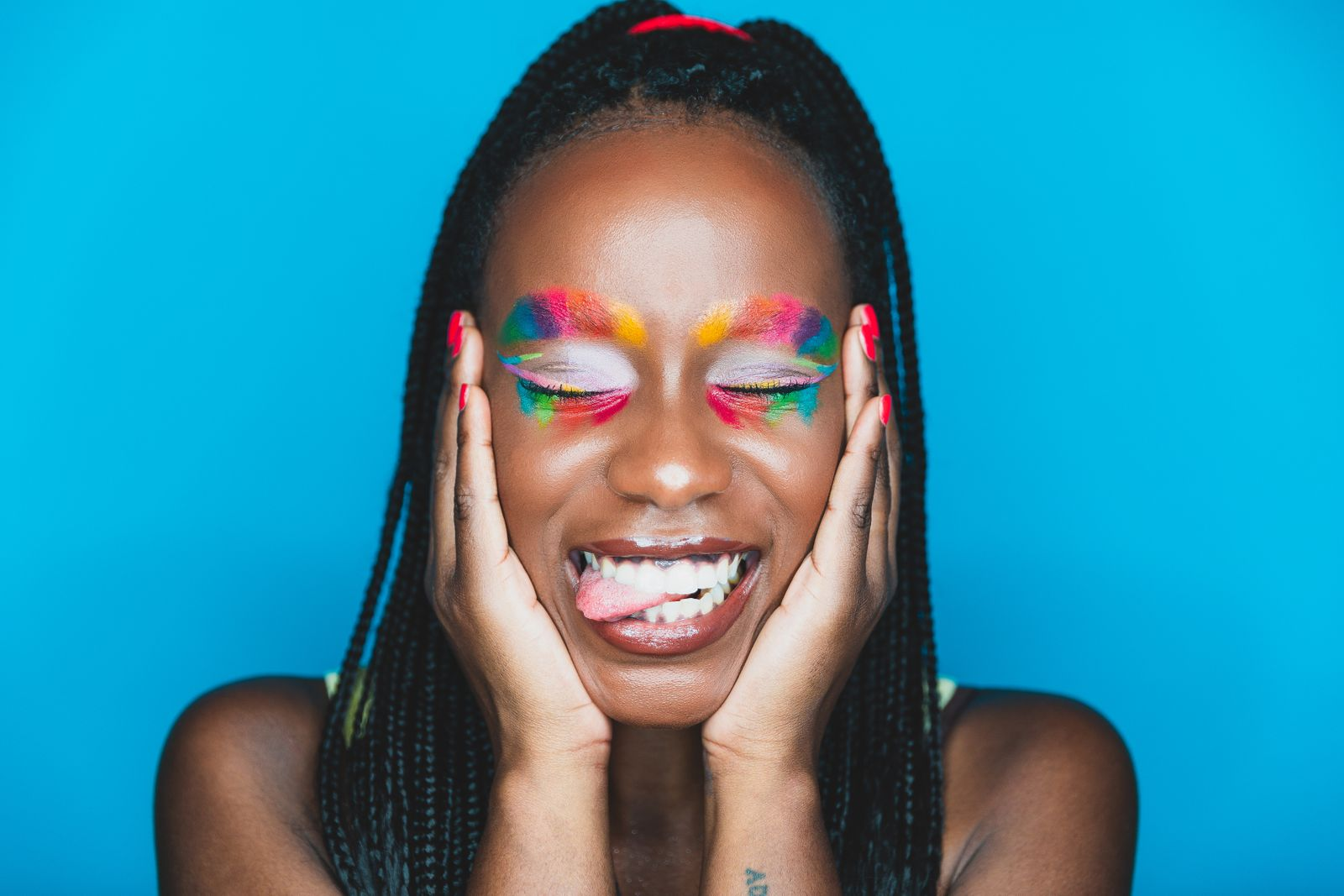 Smiling young woman posing with a rainbow colored makeup