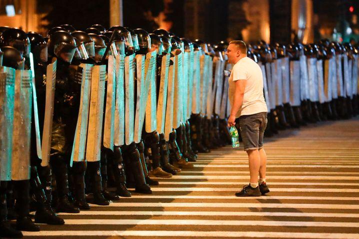 Ein Demonstrant spricht vor Sicherheitskräften, die in Minsk Stellung bezogen haben