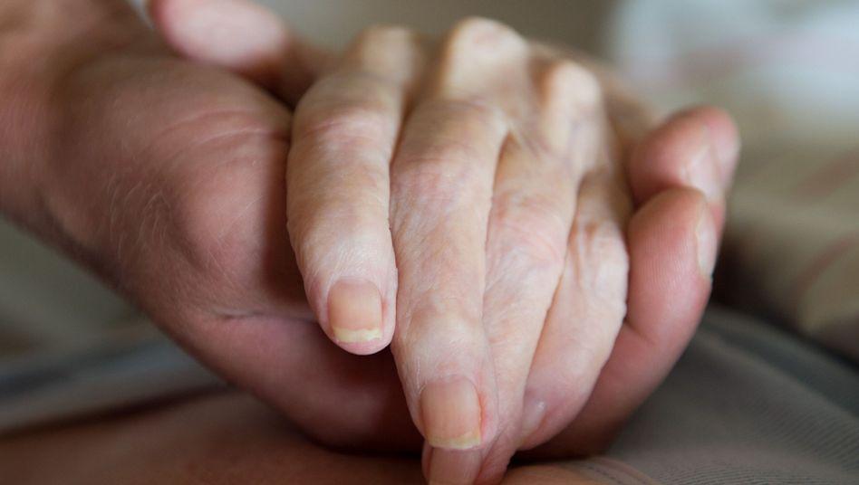 Altenpfleger hält die Hand einer Pflegebedürftigen (Archiv)