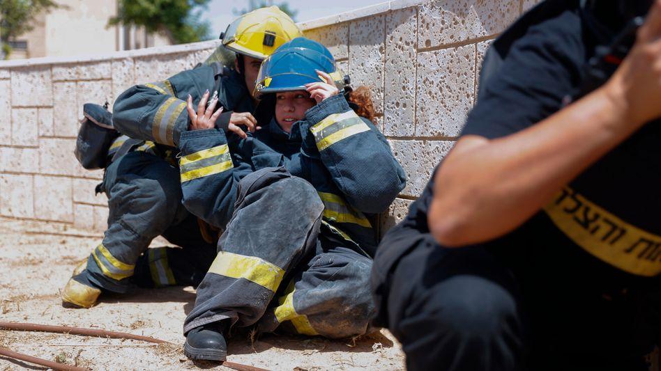 Israelische Feuerwehrleute suchen bei einem Raketenalarm Schutz hinter einer Mauer