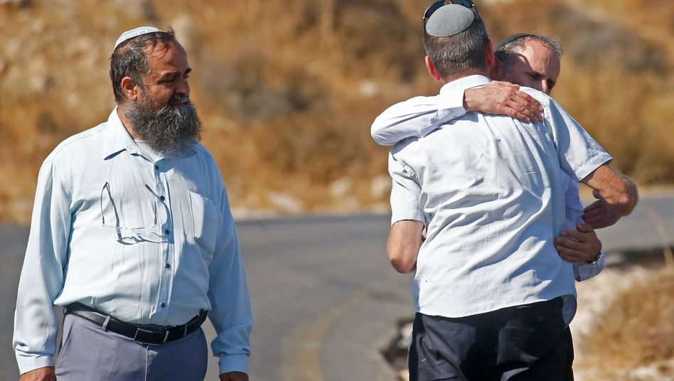 Trauernde Männer an der Fundstelle der Leiche: Der Täter wird noch gesucht