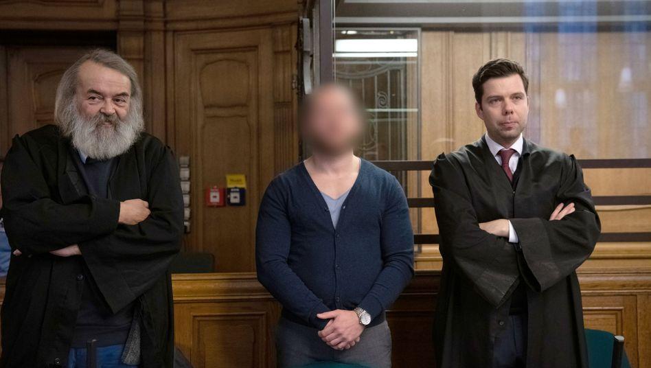 Einer der Angeklagten mit Anwälten im Kriminalgericht Moabit