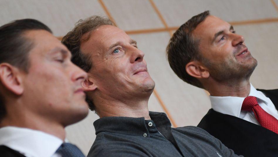 Alexander Falk (Mitte) mit seinen Verteidigern (Archivbild): Hat er jemanden angestiftet, einen Anwalt zu verletzen?