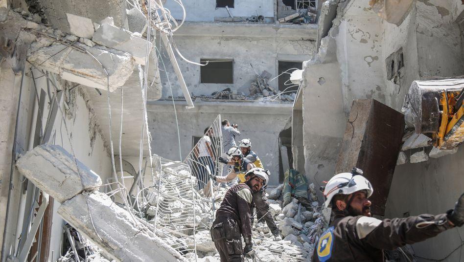 Weißhelme suchen in der Stadt Ariha nach einem Luftangriff nach Verletzten (Archivbild)