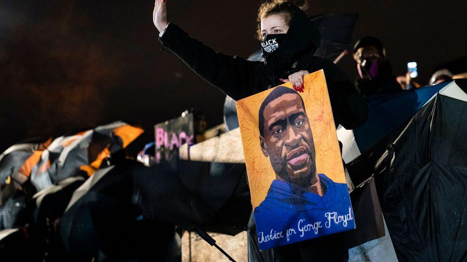 Eine Frau hält bei einer Protestaktion für den durch Polizeikugeln getöteten Schwarzen Daunte Wright ein Plakat mit der Aufschrift »Gerechtigkeit für George Floyd«