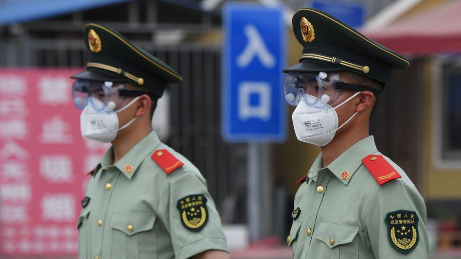 Mit Maske und Schutzbrille ausgerüstete Polizisten sperren den Eingang zum Xinfadi-Großmarkt in Peking ab
