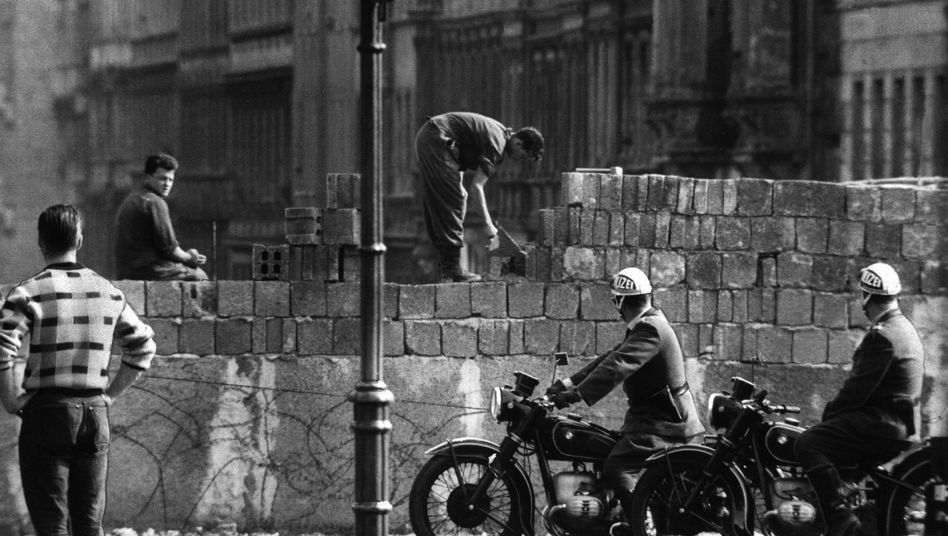 West German police and bystanders watch construction of the Berlin Wall in August 1961.