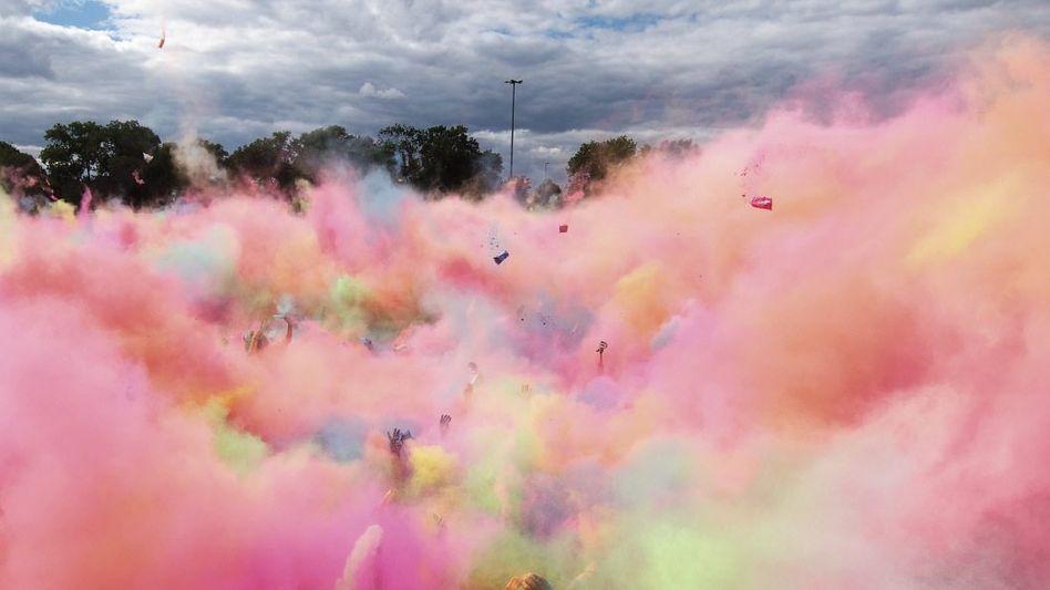 Ausgelassenes Happening: Besucher des Holi Open Air am Elbufer in Dresden werfen Farbpulver in die Luft.