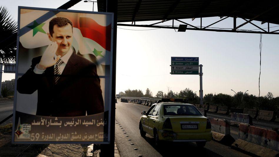 Assad-Poster am Flughafen von Damaskus: Nach acht Jahren erstmals Gespräche mit der Opposition