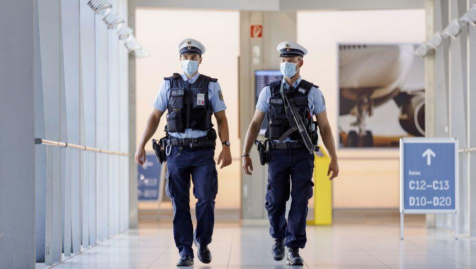 """Polizei am Flughafen Düsseldorf (Archivbild): """"Das Ziel des Infektionsschutzes ist legitim, der Eingriff zumutbar"""""""