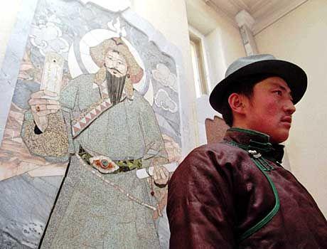 Mongole vor einem Wandmosaik Dschingis Khans: Der König wird in der Mongolei bis heute als Nationalheld verehrt