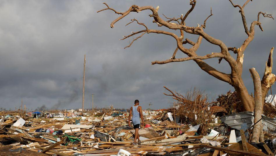 """Ein Mann läuft in Marsh Harbour auf den Bahamas über das Trümmerfeld, das """"Dorian"""" hinterlassen hat"""